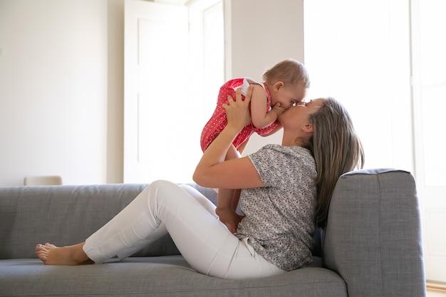 ソファに座って愛情を込めて幼い娘にキスをする愛情深い母親。手のひらで顔を閉じる幸せな女の赤ちゃん。両手で乳児を抱く長髪のお母さん。家族と母性の概念