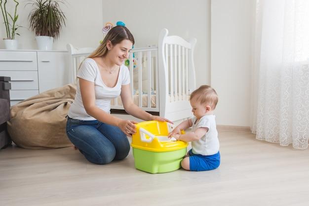 아기에게 챔버 냄비 사용법을 가르치는 사랑하는 어머니