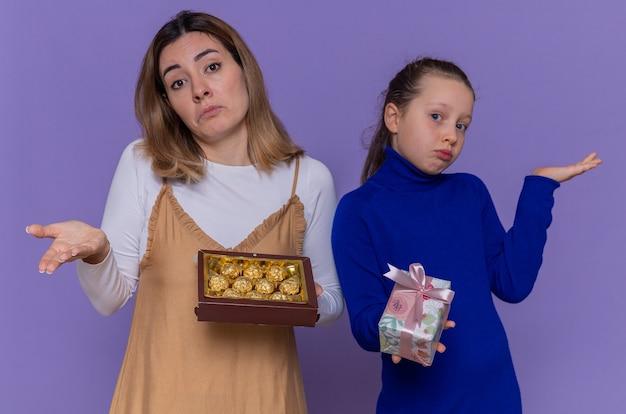 Madre amorevole con scatola di cioccolatini e figlia che tiene presente guardando confuso alzando le braccia per celebrare la giornata internazionale della donna in piedi sopra il muro viola