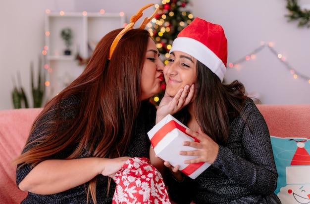 トナカイのヘッドバンドを持つ愛情のある母親は、自宅でクリスマスの時間を楽しんでソファに座ってギフトボックスを保持しているサンタの帽子で彼女の喜んでいる娘にキスします