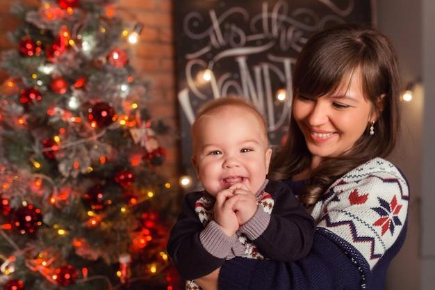 一緒に笑っているクリスマスツリーの近くで息子と愛情のある母親