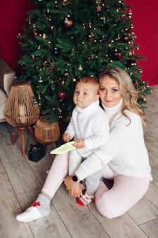 크리스마스 트리 아래 아들과 함께 사랑하는 어머니.