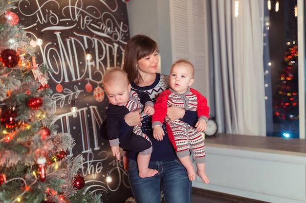 一緒に笑っているクリスマスツリーの近くに双子の息子を持つ愛情のある母親