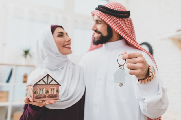 Loving muslim couple with house keys dream home.
