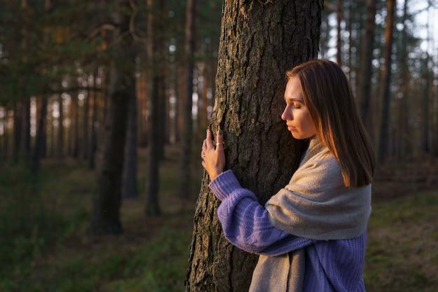 愛情のある自然の概念は、日没時に目を閉じて秋の森の木の幹を抱き締めるリラックスした女性