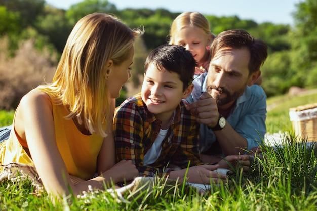 사랑하는 부모. 웃고 가족과 함께 표지에 누워있는 수염 난 아빠 경고