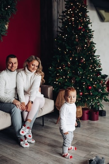 그들의 아이를 보면서 크리스마스 트리 근처 소파에 앉아 흰 옷을 입은 사랑하는 부모