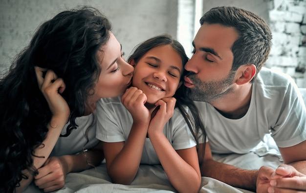 ベッドに横たわっている娘にキスをする愛情深い両親