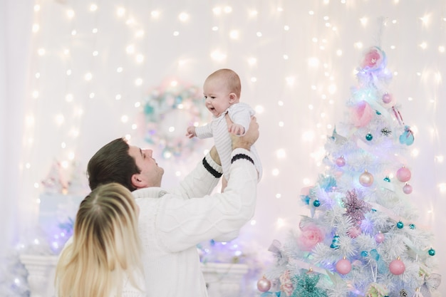 Любящие родители играют со своим малышом в канун рождества. концепция семейного счастья