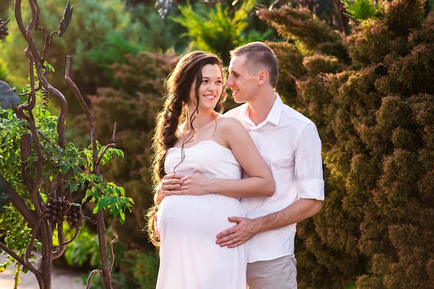A loving pregnant couple hugs in a summer park and smiles