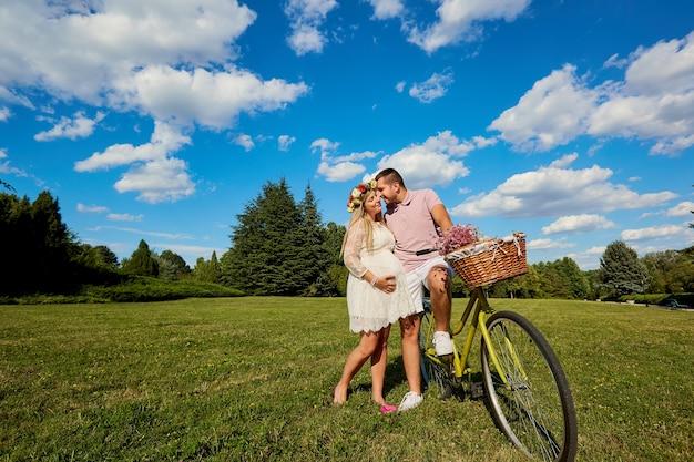Влюбленная беременная пара в парке, обнимая летние поцелуи, улыбается, счастливые и радостные муж и жена беременны в ожидании ребенка