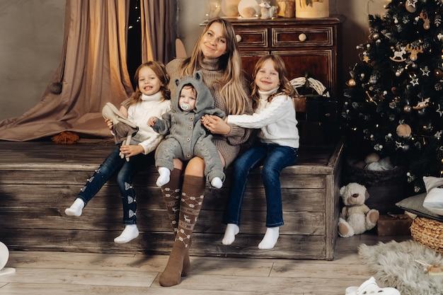 ニットのニーソックスとドレスを着たかわいいお母さんが、かわいい赤ちゃんの息子を太ももに抱き、2人の娘が横に座っています。クリスマスのための装飾された部屋。