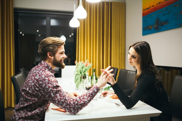 Loving romantic couple holding hands at table