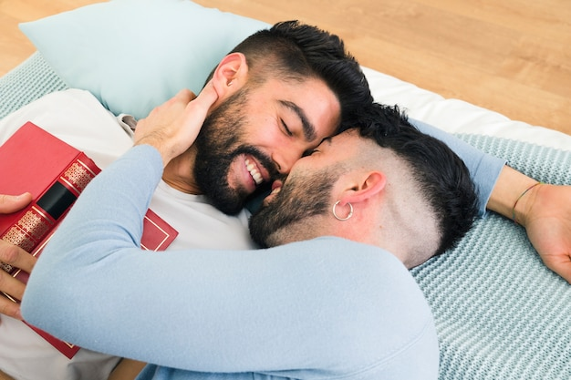 Loving romantic young gay couple lying on bed