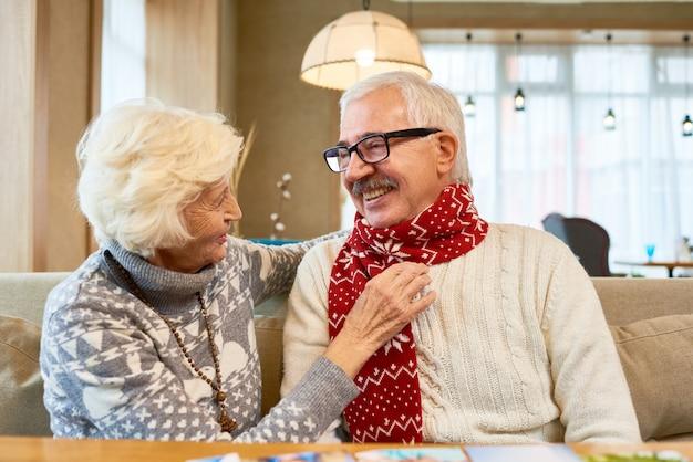 Любящая старшая пара, обменивающая подарки на рождество