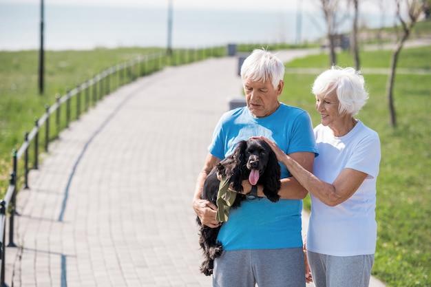 Loving senior couple holding pet dog