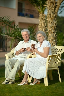 Loving senior couple sitting on chairs with coffee in tropical garden