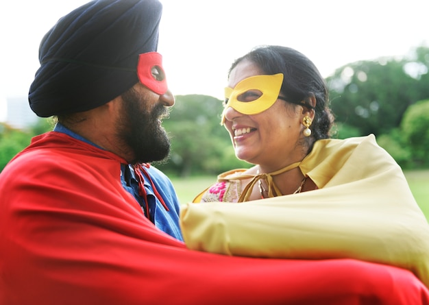 Loving senior indian couple playing superheroes