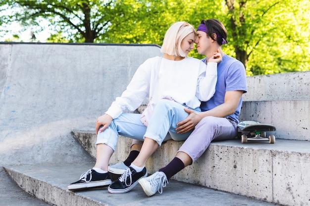 Влюбленная пара подростков в скейт-парке