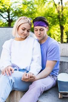 Влюбленная пара подростков в скейтпарке