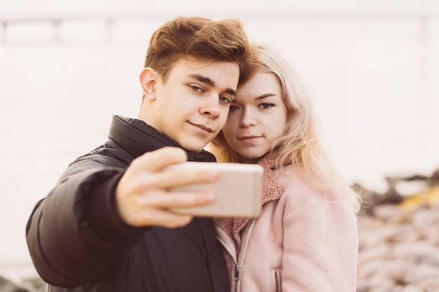 Loving teenagers on date. cute brunette boy and beautiful blonde girl take a selfie on a cell phone