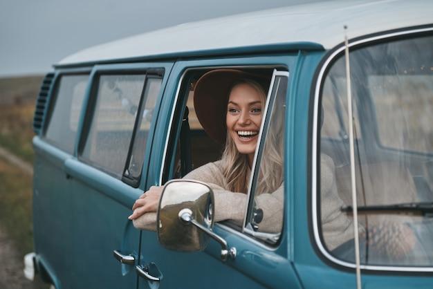 このロードトリップが大好きです。バンの窓の外を見て、車の旅を楽しみながら笑っている魅力的な若い女性