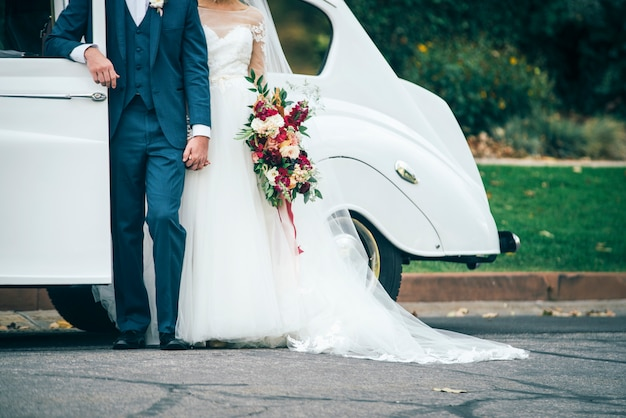 Loving wedding couple is staying near the old car with bouquet