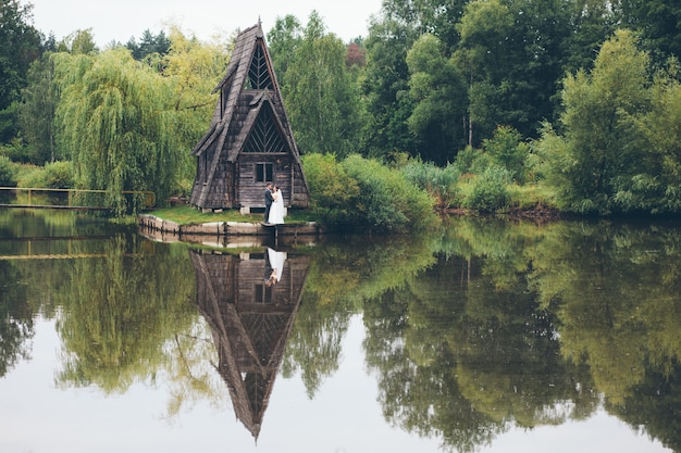 Loving wedding couple near a beautiful house on the lake in the woods