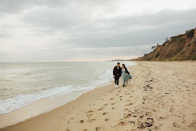해변에 산책하는 웨딩 커플 사랑. 바다로 그들의 결혼식 사진 촬영에 아름다운 웨딩 커플