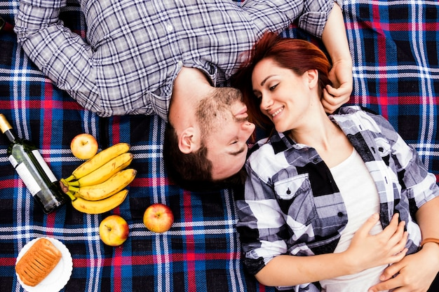 Loving woman with her husband lying on blanket with many fruits