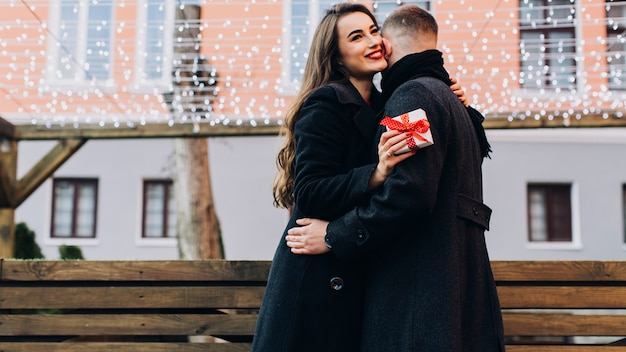 Loving woman with present embracing man