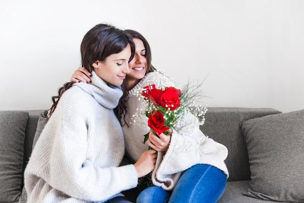 ソファーにバラを持つ女性を愛する