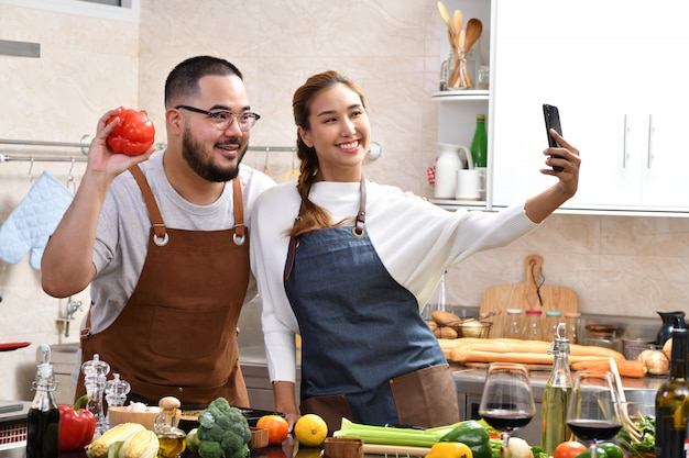 Влюбленная молодая азиатская пара готовит на кухне, вместе готовит здоровую пищу и чувствует себя весело и с помощью смартфона делает селфи