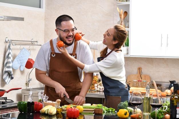 一緒に楽しく健康的な食品を作るキッチンで料理をしてアジアの若いカップルを愛する