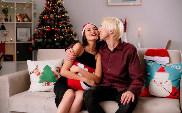 Влюбленная молодая пара дома на рождество в шляпе санта-клауса сидит на диване в гостиной девушка держит рождественскую подушку, парень обнимает ее, целует ее в щеку