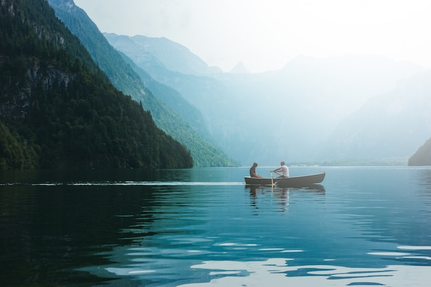 Loving young couple in boat at lake. date walk man and woman in alpine mountains