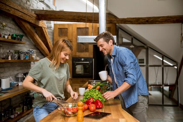 素朴なキッチンで若いカップルカット野菜を一緒に愛する