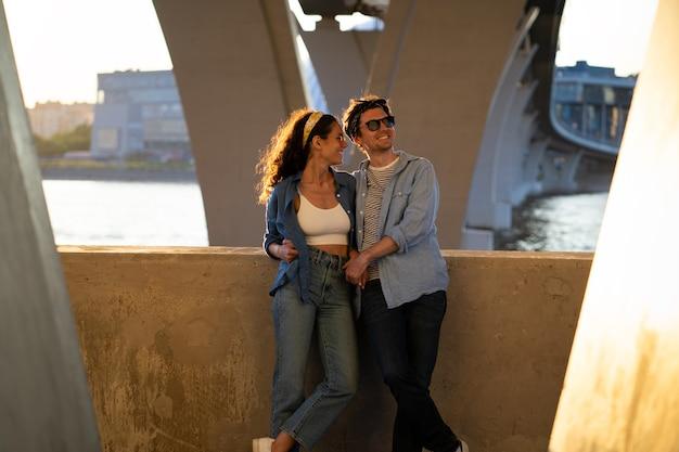 日没のトレンディなカジュアルな男性と女性を抱きしめる愛情のある若いカップルは、一緒に時間を過ごすことを楽しんでいます