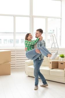 Любящая молодая пара, радуясь переезду в свой новый дом, концепция переезда