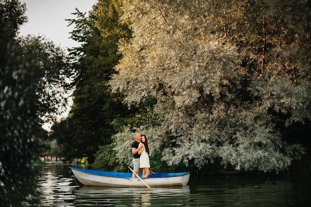 湖でボートを楽しむ若いカップルを愛する