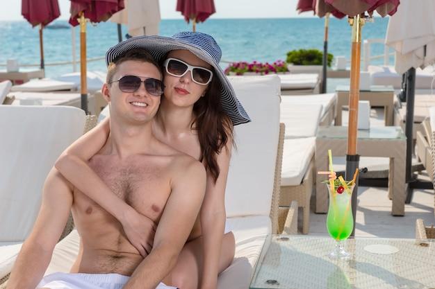 Любящая молодая пара наслаждается летними каникулами, расслабляясь в интимных объятиях на тропическом курорте на берегу моря в кресле с откидным верхом