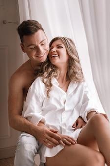 バレンタインの日に窓の近くの家で朝を楽しんでいる若いカップルを愛する。白いシャツと半分裸で一緒に楽しんでいる男の女の子