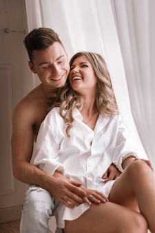 Loving young couple enjoying morning at home near the window on valentine's day. girl in white shirt and guy half naked having fun together