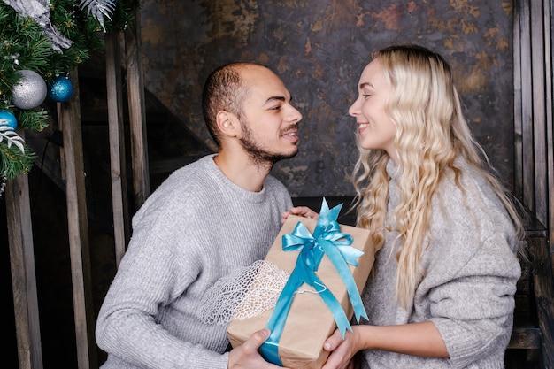 사랑하는 젊은 부부가 새해 선물을 교환합니다.