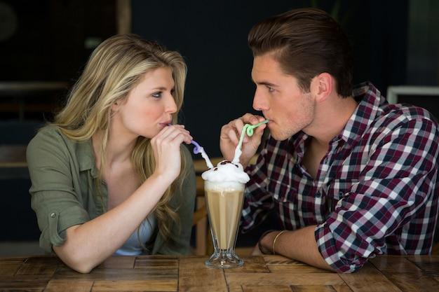 コーヒーショップのテーブルでミルクセーキを持っている愛情のある若いカップル