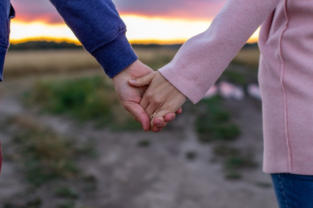 Loving young couple holding hands. hands of a girl and a guy close-up.