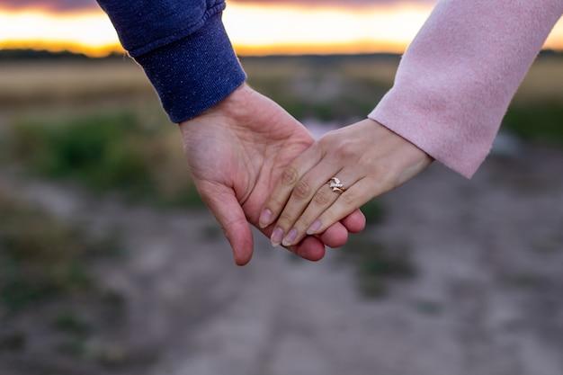 Любящая молодая пара, держась за руки. руки девушки и парня крупным планом.