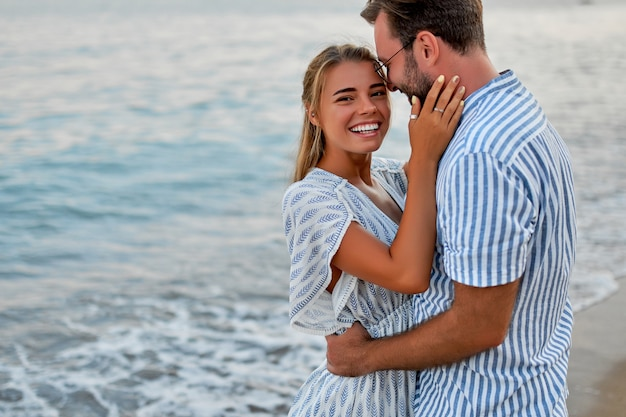 A loving young couple hug on the seashore, enjoying each other and their vacation, romantically spending time on the beach.