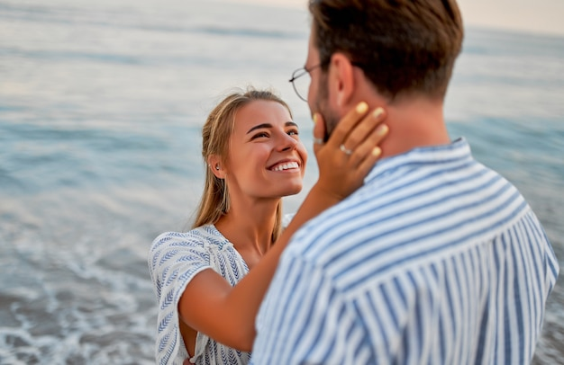 A loving young couple hug on the seashore, enjoying each other and their vacation. a woman in a dress and a man in a shirt are romantically spending time on the beach.