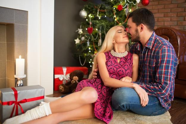 Влюбленная пара обнимает, сидя на меховом коврике возле новогодних елок и подарков
